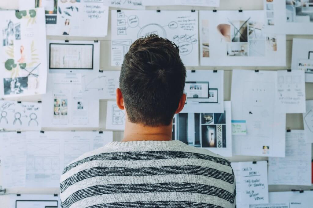 A person from behind, looking onto a big board full of scribbles and text. Serving as an example of how UX Researchers are working to deepen the insights they have collected.